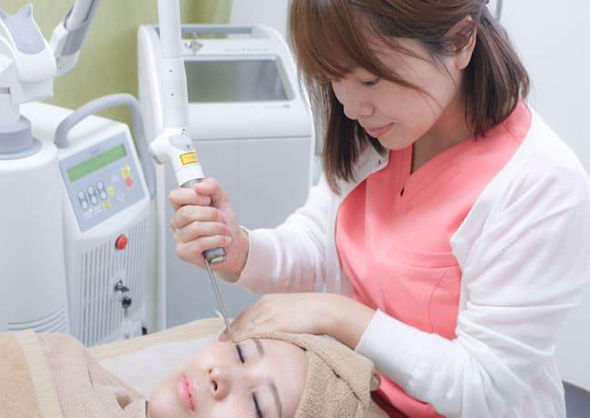 当院で使用する医療用レーザー機器Fotona QX(フォトナ)」でシミ」・くすみ治療をしている様子